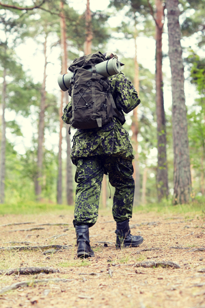 infantryman: war, hiking, army and people concept - young soldier, ranger or hunter with backpack walking in forest