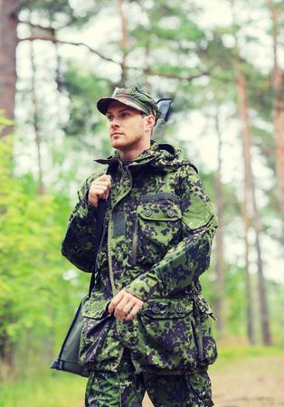 cazador: la caza, la guerra, el ejército y el pueblo concepto - joven soldado, guardabosques o un cazador con arma de fuego que recorre en bosque Foto de archivo
