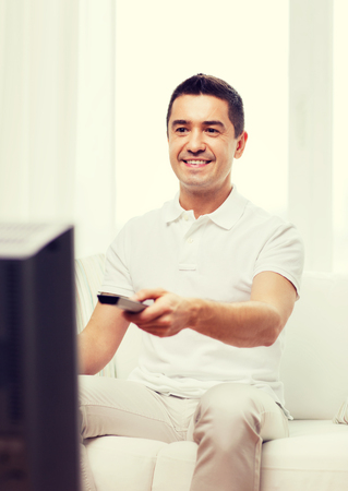 entertainment concept: home, people, technology and entertainment concept - smiling man with remote control watching tv at home Stock Photo