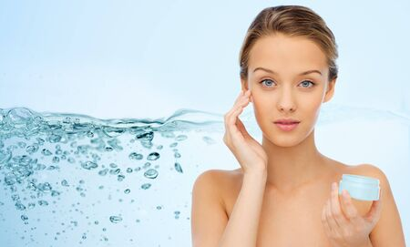 splash of water: beauty, people, moisturizing, skin care and cosmetics concept - young woman applying cream to her face over water splash background