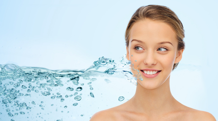 beauty, people and health concept - smiling young woman face and shoulders over water splash and blue background