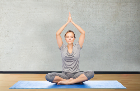 meditation room: fitness, sport, people and healthy lifestyle concept - woman making yoga meditation in lotus pose on mat over gym room background Stock Photo