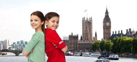 childhood, travel, tourism and people concept - happy smiling boy and girl standing back to back over london city background Stock Photo