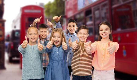 young group: childhood, travel, tourism, gesture and people concept - happy smiling children showing thumbs up over london city street background Stock Photo