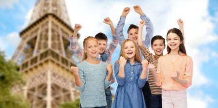 youth group: childhood, travel, tourism, gesture and people concept - happy children friends raising fists and celebrating victory over paris eiffel tower background