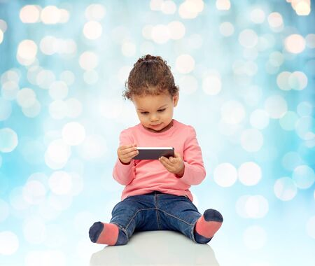 two year: childhood, technology and people concept - smiling little african american baby girl playing with smartphone and sitting on floor over blue holidays lights background