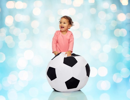 baby playing: childhood, game, sport, football and people concept - happy african american little baby girl playing with ball over blue holidays lights background Stock Photo