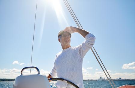 lejos: la vela, la edad, el turismo, los viajes y el concepto de la gente - hombre mayor feliz en el sombrero de capitán en el volante y mirando a lo lejos velero o yate que flota en el mar