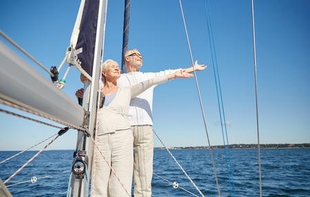 세일링, 연령, 관광, 여행 및 사람들이 개념 - 행복 한 고위 커플 바다에 떠있는 항해 보트 또는 요트 갑판에 자유를 즐기고