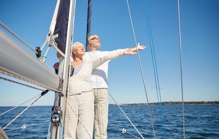 sailing, age, tourism, travel and people concept - happy senior couple enjoying freedom on sail boat or yacht deck floating in sea Stok Fotoğraf - 58613871