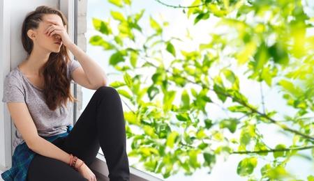 ludzie, emocje i młodzieży koncepcji - smutny nieszczęśliwy całkiem nastoletnich dziewczyna siedzi na parapecie nad letnich brunch drzewa tle Zdjęcie Seryjne