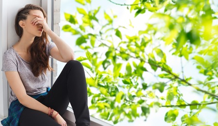 people, emotion and teens concept - sad unhappy pretty teenage girl sitting on windowsill over summer tree brunch background