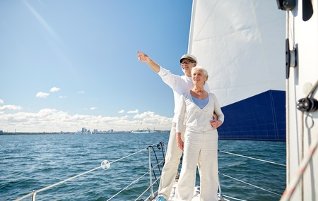 sail boat: sailing, age, tourism, travel and people concept - happy senior couple pointing finger to something on sail boat or yacht deck floating in sea