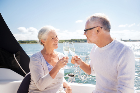 old boat: sailing, age, travel, holidays and people concept - happy senior couple clinking champagne glasses on sail boat or yacht deck floating in sea Stock Photo