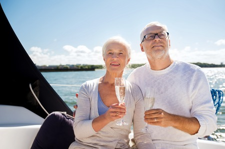 sparkling wine: sailing, age, travel, holidays and people concept - happy senior couple with champagne glasses on sail boat or yacht deck floating in sea
