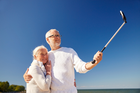 taking a wife: age, travel, tourism, technology and people concept - happy senior couple with smartphone on selfie stick taking picture on summer beach Stock Photo