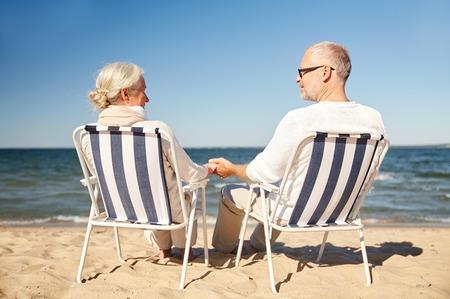 familie, leeftijd, reizen, toerisme en mensen concept - gelukkig senior paar rusten in klapstoelen op de zomerstrand van rug