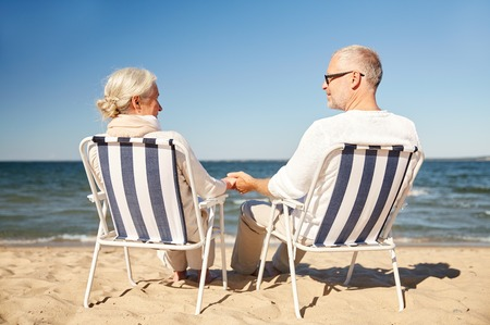 seniors couple: family, age, travel, tourism and people concept - happy senior couple resting in folding chairs on summer beach from back Stock Photo