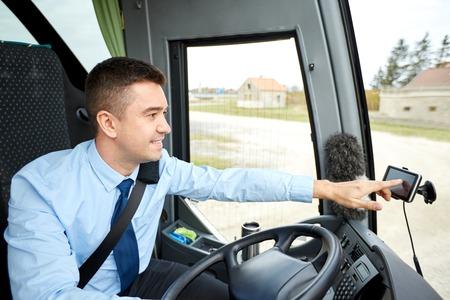 chofer de autobus: el transporte, el transporte, la navegación y el concepto de la gente - conductor del autobús, introduciendo la dirección de navegador GPS