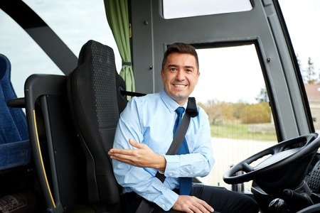 inviting: transport, tourism, road trip, gesture and people concept - happy driver inviting on board of intercity bus