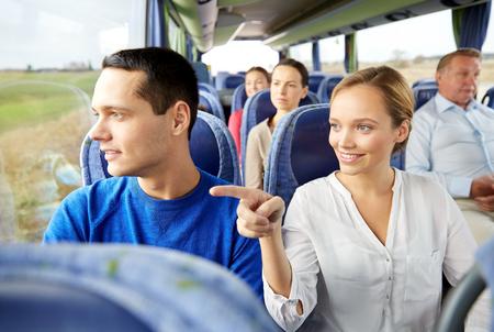 Verkehr, Tourismus, Autoreise und Menschen Konzept - glückliches Paar mit Gruppe von glücklichen Passagiere oder Touristen in Reisebus