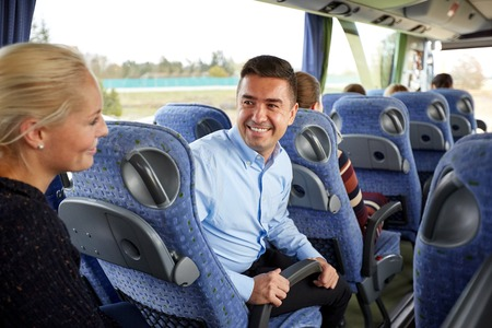 flirt: transport, tourism, road trip and people concept - group of happy passengers or tourists in travel bus