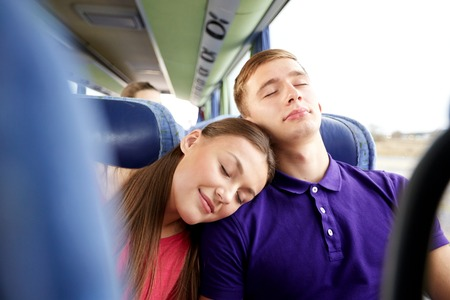 transport, tourism, road trip and people concept - happy teenage couple or tourists sleeping on shoulder in travel bus Stock Photo