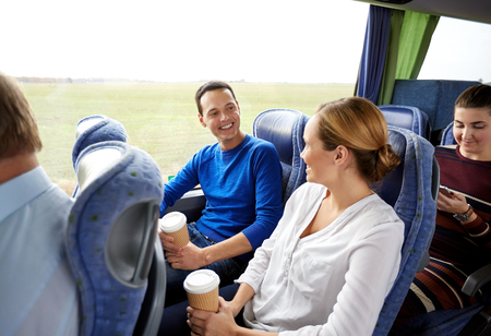 transport, tourism, road trip and people concept - group of happy passengers or tourists in travel bus