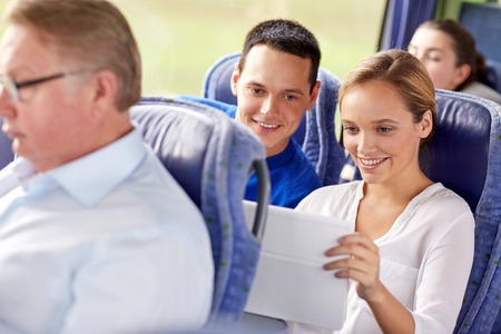 transport, tourism, road trip, technology and people concept - happy couple with tablet pc in travel bus