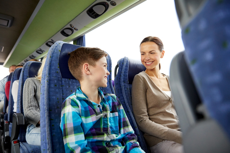travel, tourism, family, technology and people concept - happy mother and son riding in travel bus Foto de archivo
