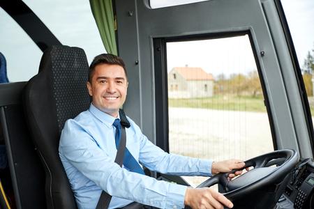 transporte, turismo, viaje por carretera y la gente concepto - controlador feliz conducción de autobuses interurbanos