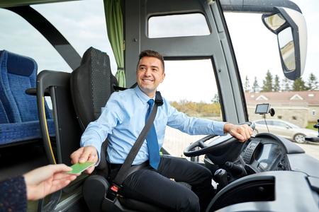 транспорт, туризм, путешествие на автомобиле, и люди концепции - улыбается водитель автобуса брать билет или пластиковую карту от пассажира Фото со стока