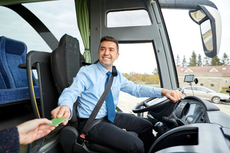 transport, turystyka, podróż drogi i koncepcja ludzi - uśmiecha kierowcę autobusu biorąc bilet lub plastikową kartę z pasażerem Zdjęcie Seryjne