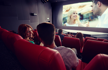 cinema, entertainment, communication and people concept - happy couple of friends watching movie and talking in theater from back