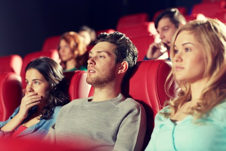 thriller: cinema, entertainment and people concept - happy friends watching horror, drama or thriller movie in theater