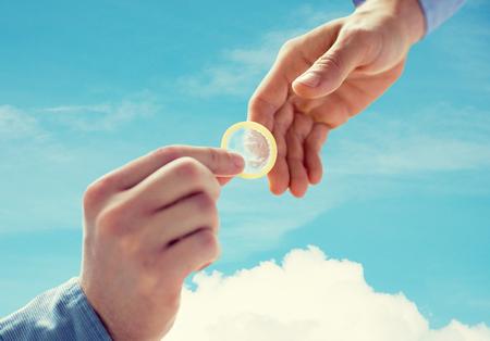 educacion sexual: personas, homosexualidad, sexo seguro, la educación sexual y el concepto de la caridad - Cerca de feliz pareja manos de los homosexuales varones que dan condón sobre el cielo azul y nubes de fondo