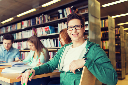 people, knowledge, education and school concept - happy student boy reading books in library