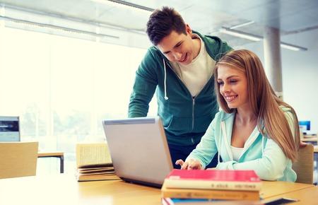 Menschen, Bildung, Technologie und Konzept der Schule - glückliche Kursteilnehmer mit Laptop-Computer-Vernetzung in der Bibliothek