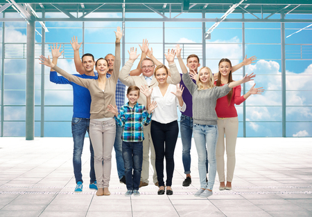 arrival: travel, vacation and people concept - group of happy people or big family waving hands over airport terminal window and sky background Stock Photo