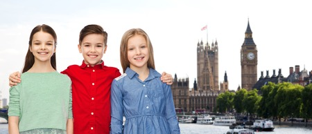 britain: childhood, travel, tourism, friendship and people concept - happy smiling boy and girls hugging over london city background Stock Photo
