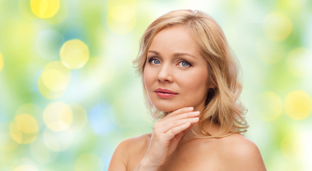 bare shoulders: beauty, people and skincare concept - woman with bare shoulders touching face over green summer lights background Stock Photo