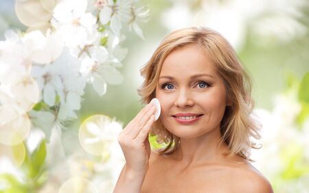 removing make up: beauty, people, skincare and natural cosmetics concept - young woman cleaning face and removing make up with cotton pad over cherry blossom background