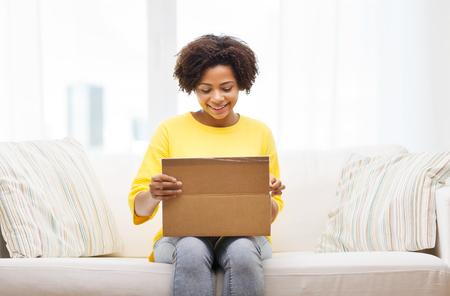 boite carton: les gens, la livraison, le transport maritime et le concept de service postal - Happy Box afro-américaine jeune femme d'ouverture de carton ou un colis à la maison Banque d'images