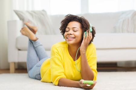 listening to music: las personas, la tecnología y el concepto de ocio - feliz mujer joven afroamericana tirado en el suelo con el teléfono inteligente y los auriculares escuchando música en casa