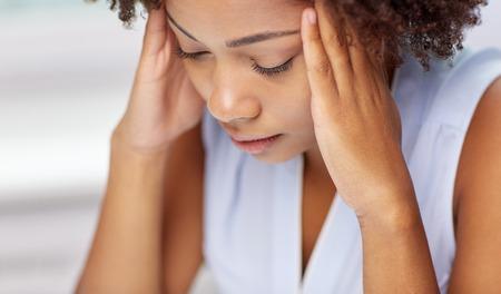 occhi tristi: le persone, le emozioni, lo stress e il concetto di assistenza sanitaria - infelice African American giovane donna di toccare la sua testa e che soffrono di mal di testa Archivio Fotografico