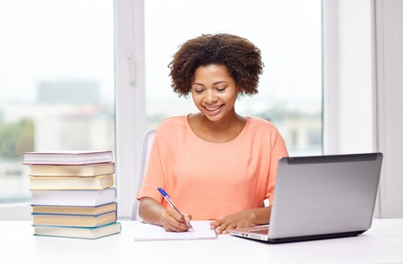 persona escribiendo: las personas, la tecnología y el concepto de la educación - feliz mujer joven afroamericano sentado en la mesa con el ordenador portátil y los libros en el hogar