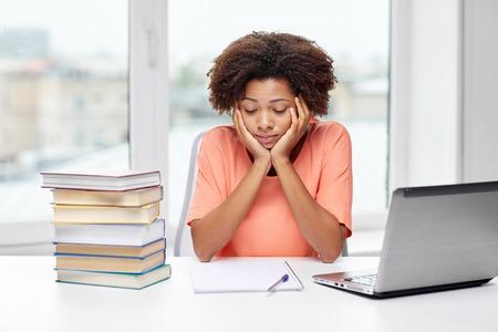 adolescente pensando: las personas, la tecnología y el concepto de la educación - aburrido joven mujer afroamericana sentado en la mesa con el ordenador portátil, libros y bloc de notas en el hogar