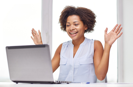online education: education, business, success and technology concept - happy african american businesswoman or student with laptop computer and papers at office