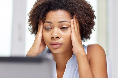 onderwijs, bedrijfsleven, mislukken en technologie concept - Afro-Amerikaanse zakenvrouw of student met een laptop computer en papieren op kantoor