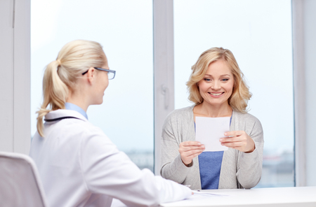 woman middle age: medicine, health care, meeting and people concept - smiling doctor giving medical prescription or certificate to woman at hospital